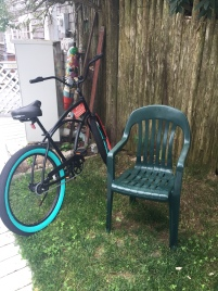 Green bicycle and lawn chair