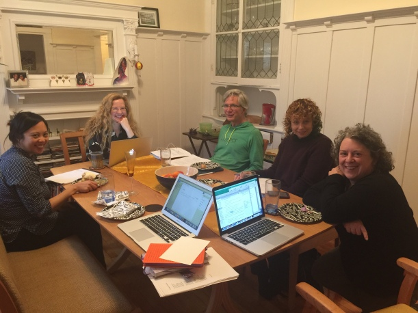 Five people seated around a table smiling, laptops and notebooks open during the first writing session for Four Chairs & a Bench.