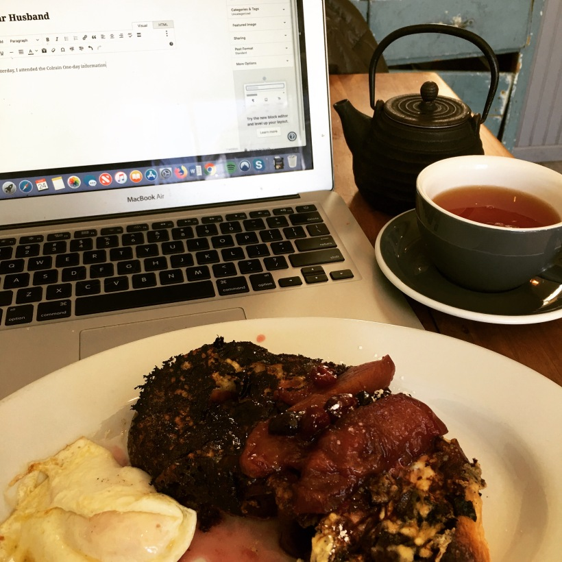 Plate of french toast and fried egg in the foreground; open laptop in the background with cup of Earl Grey tea and teapot