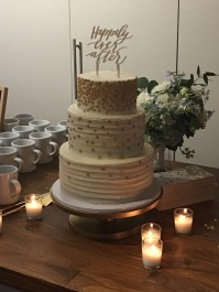 Three-tiered cake with white frosting and gold decorations with Happily Ever After topper